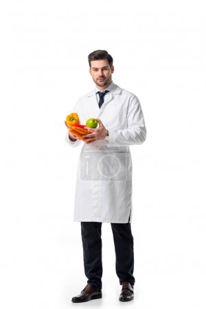 nutritionist in white coat with fresh vegetables and apple in hands isolated on white