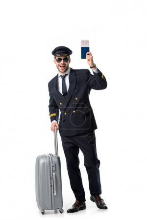 happy pilot with luggage, passport and ticket isolated on white