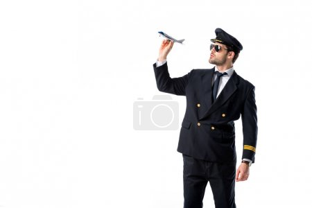 young bearded pilot in uniform and sunglasses with toy plane isolated on white