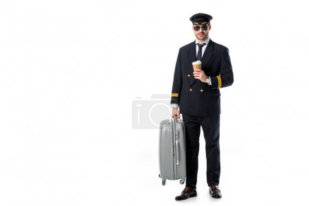 young pilot in uniform and sunglasses with coffee to go and luggage isolated on white
