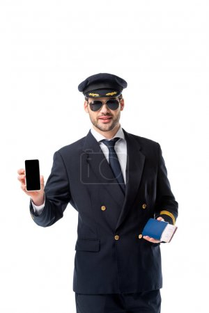 portrait of pilot in uniform with passport and ticket in hand showing smartphone with blank screen isolated on white