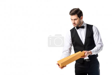 portrait of young waiter in suit vest with menu isolated on white