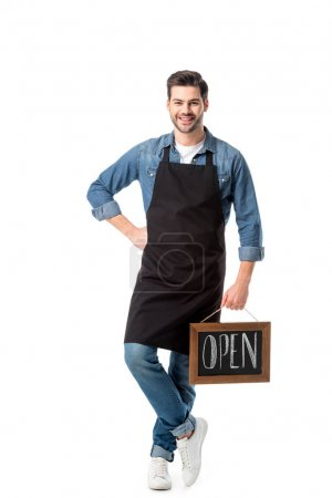 Photo for Smiling young waiter with open blackboard isolated on white - Royalty Free Image