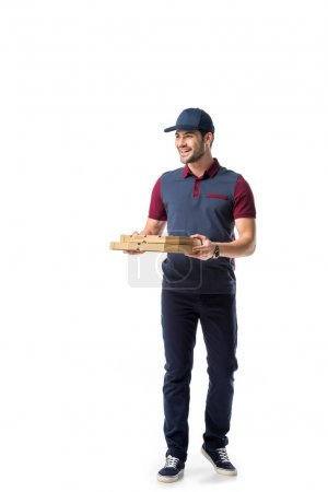 smiling delivery man with cardboard pizza boxes looking away isolated on white