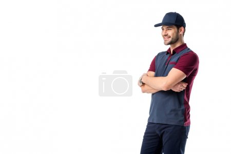 side view of smiling delivery man in cap with arms crossed isolated on white