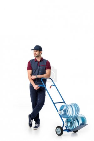 smiling delivery man with large bottles of water on hand truck isolated on white