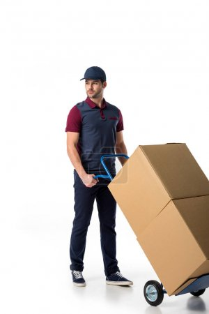 delivery man in uniform pushing hand truck with cardboard boxes isolated on white
