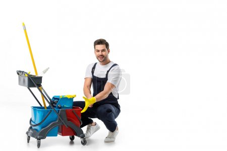 smiling cleaner in uniform and rubber gloves with cart isolated on white