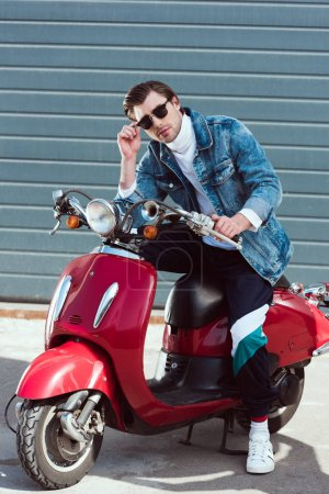 handsome young man on vintage red scooter looking at camera