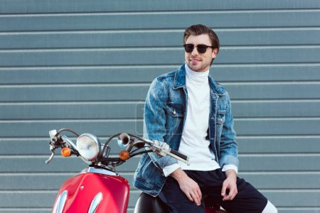 happy young man in denim jacket on vintage red scooter