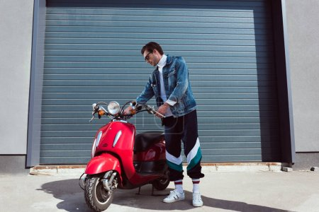 handsome young man in denim jacket and track pants with vintage red scooter