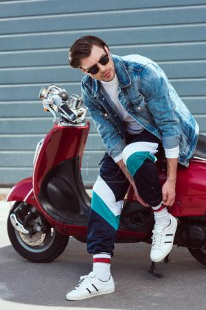 young man in stylish denim jacket with vintage scooter