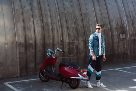 stylish young man in stylish denim jacket with vintage scooter on parking