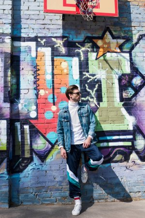 handsome young man in vintage clothing leaning on brick wall with graffiti