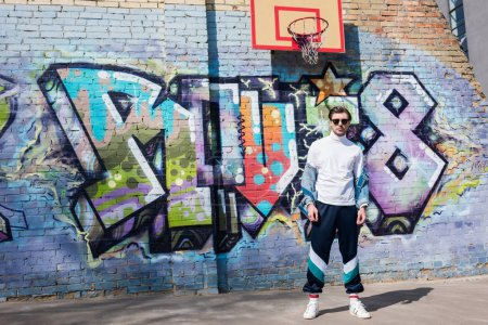 stylish young man in vintage clothing in front of brick wall with graffiti and basketball ring
