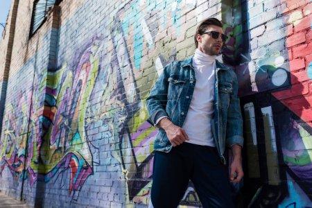 Photo pour Jeune élégant dans des vêtements vintage, s'appuyant sur le mur de briques avec des graffitis - image libre de droit
