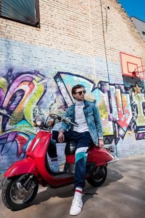 handsome young man in stylish clothes on vintage red scooter in front of brick wall with graffiti