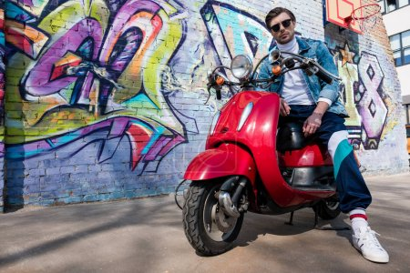 handsome young man on vintage red scooter looking at camera in front of brick wall with graffiti