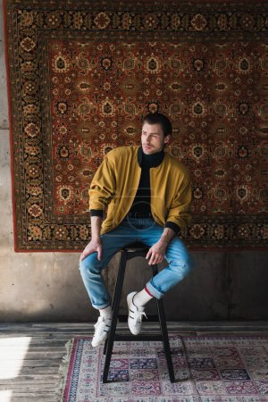 stylish young man sitting on chair in front of rug hanging on wall
