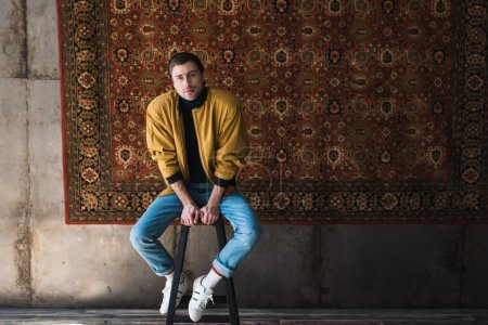 young man in yellow jacket sitting on chair in front of rug hanging on wall