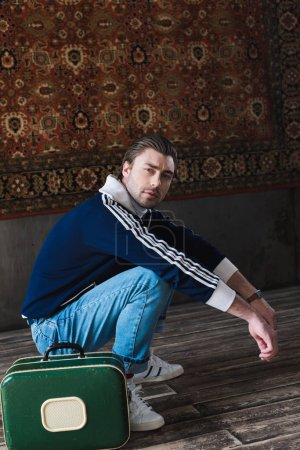 young man with vintage little suitcase sitting squat in front of rug hanging on wall