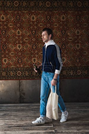 young man in old school clothes with string bag and bottle of beer in front of rug hanging on wall