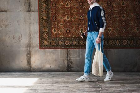 cropped shot of man in old school clothes with string bag and bottle of beer in front of rug hanging on wall