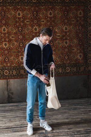 man in old school clothes putting bottle of beer into string bag in front of rug hanging on wall