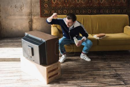young man in vintage clothes with bottle of milk punching old tv
