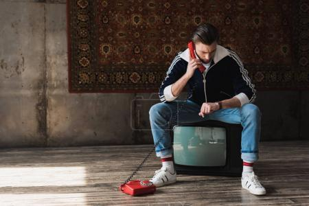 Foto de Atractivo joven en ropas de época sentado en la tv retro y hablando por teléfono y mirando el reloj delante de alfombra colgada en pared - Imagen libre de derechos