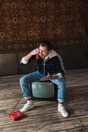 Photo for Angry young man in vintage clothes sitting on retro tv set and talking by phone in front of rug hanging on wall - Royalty Free Image