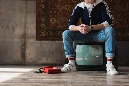 handsome young man in vintage clothes sitting on retro tv set near red wired telephone in front of rug hanging on wall
