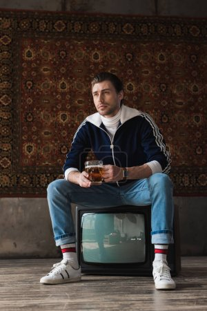 stylish young man in vintage clothes with mug of beer sitting on retro tv set in front of rug hanging on wall