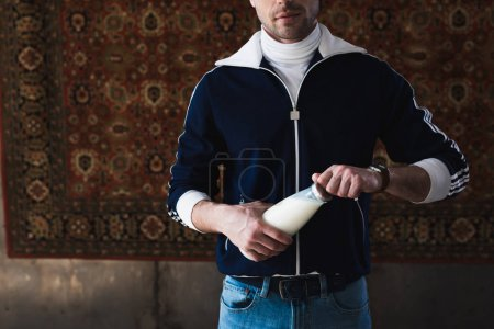 cropped shot of young man in vintage clothes with bottle of milk in front of rug hanging on wall