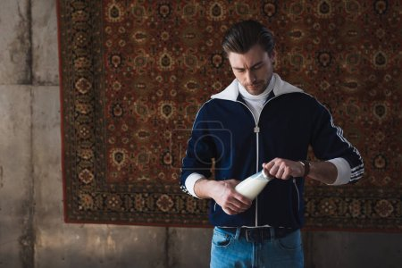 handsome young man in vintage clothes with bottle of milk in front of rug hanging on wall