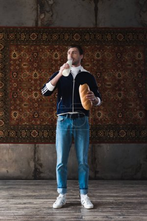 handsome young man in vintage clothes with bottle of milk and loaf of bread in front of rug hanging on wall