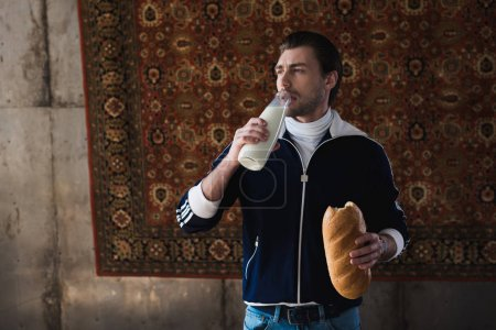 young man in vintage clothes with bottle of milk and loaf of bread in front of rug hanging on wall