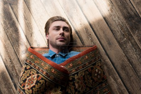 top view of handsome young man covered in rug lying on wooden floor