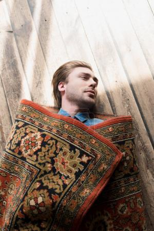 top view of young man covered in rug lying on wooden floor