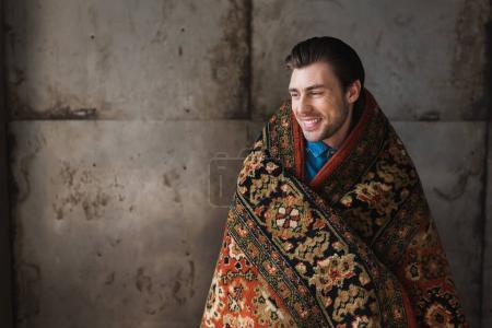 Photo for Happy young man covered in rug in front of concrete wall - Royalty Free Image