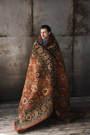 handsome young man covered in rug in front of concrete wall