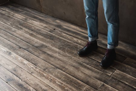 cropped shot of man in stylish jeans and boots standing on wooden floor
