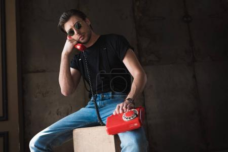 handsome young man in black t-shirt and sunglasses talking by retro wired red phone