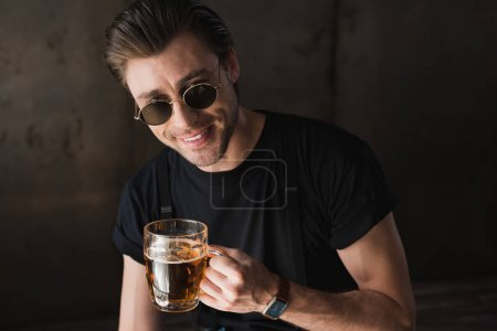 smiling young man in black t-shirt and sunglasses holding mug of beer and looking at camera