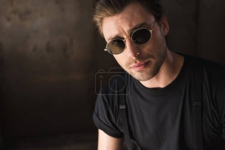 close-up portrait of handsome young man in black t-shirt and sunglasses looking at camera