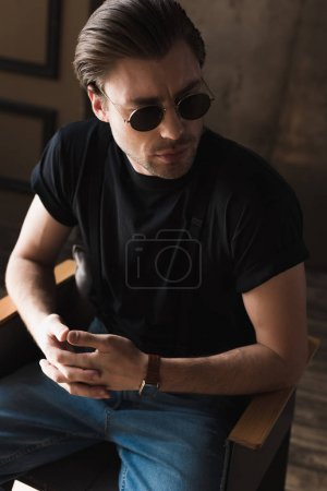 attractive young man in black t-shirt and sunglasses sitting on chair