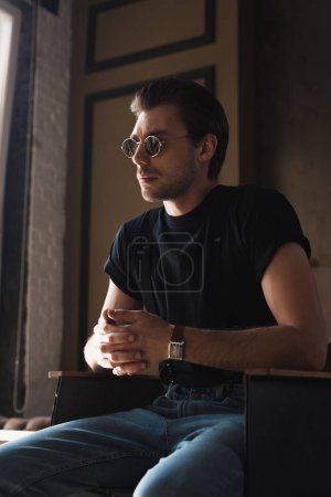 Photo for Young man in black t-shirt and sunglasses sitting on chair - Royalty Free Image