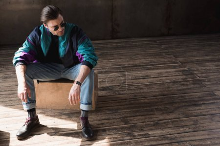 stylish young man in vintage windcheater sitting on wooden box in loft room