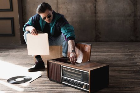 handsome nostalgic man in vintage windcheater with vinyl record player