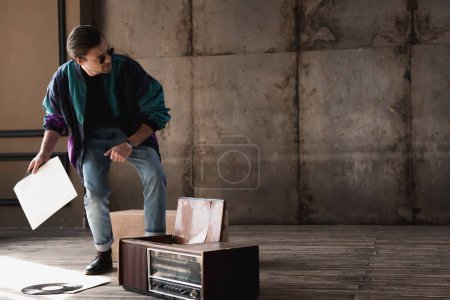 stylish young man in vintage windcheater with vinyl record player
